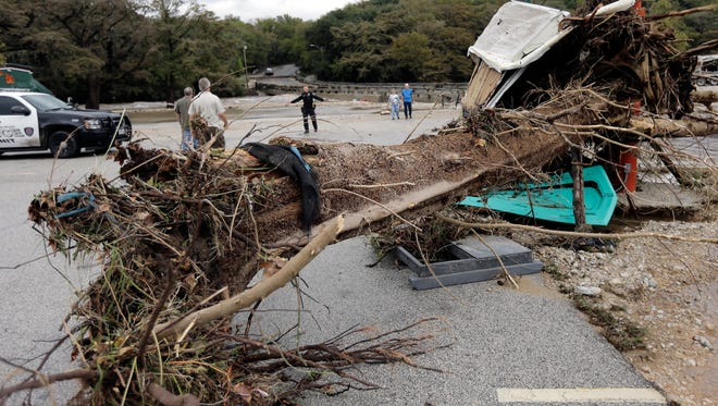 A police officer, center, works to vacate an area damaged by flood waters Friday, Oct. 30, 2015, in Gruene, Texas. Storms on Friday socked an already sodden swath of Texas that was still drying out from the remnants of Hurricane Patricia, forcing evacuations and shutting down a busy 10-mile stretch of interstate. (AP Photo/Eric Gay)