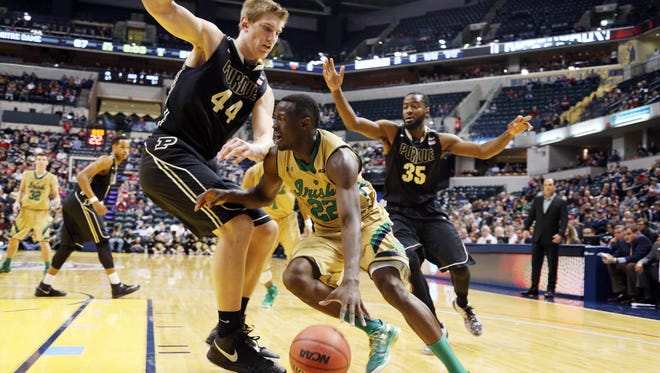 Dec 20, 2014; Indianapolis, IN, USA; Notre Dame Fighting Irish guard Jerian Grant (22) drives baseline against Purdue Boilermakers center Isaac Haas (44) during the Crossroads Classic at Bankers Life Fieldhouse. Notre Dame defeats Purdue 94-63. Mandatory Credit: Brian Spurlock-USA TODAY Sports