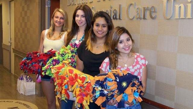 Lindsey Bijas, Amanda Sorrentino, Alexandra Callirgos and Michelle Fernandez visit the Outpatient Infusion Unit at the Leon Hess Cancer Center at Monmouth Medical Center to deliver knot blankets to patients.