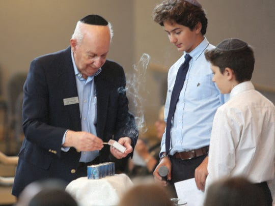 Holocaust survivor Rob Nossen lights a candle with the help of his sixth-grade biographers during the Yom Hashoah: Holocaust Remembrance Day event Sunday, April 23, 2017, at Temple Shalom.