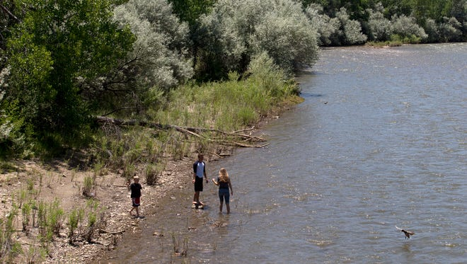 Hyrum Frey, left, Joshua Frey and Rachel Corbett play along the Animas River Thursday at Berg Park in Farmington. Restoration work on the river is being partially funded by a federal program.