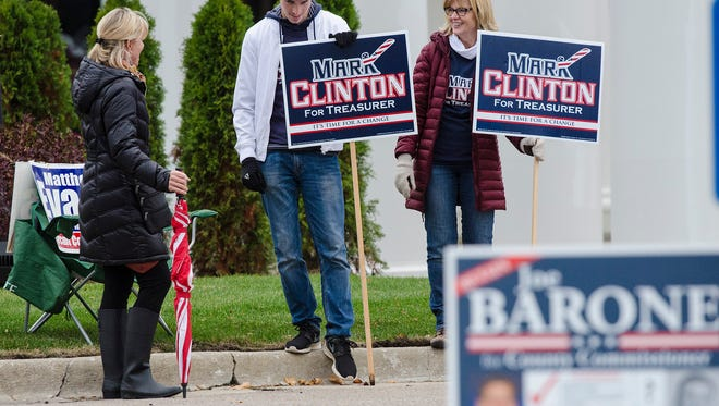In Plymouth Township, the family of the other Clinton, Mark Clinton, running for treasurer, holds campaign signs outside the polls at Northridge Church. Carol Clinton and son Kyle Clinton, speak with neighbor Ann Houska.