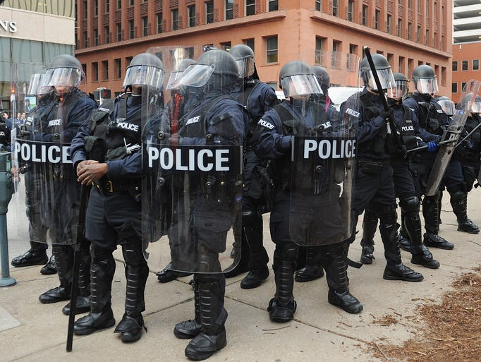 Police officers stand on alert after an arrest  during
