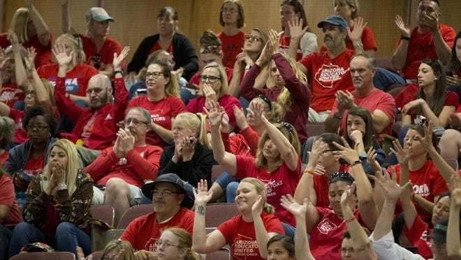 Red For Ed supporters wave their hands to show support during the House of Representatives budget meeting at the state Capitol in Phoenix, Ariz., on May 3, 2018.