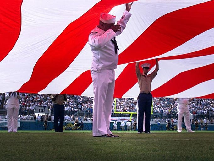 Kenneth Jones, center, of the U.S. Navy wipes his eye as he hold up the American Flag during the opening ceremonies of the Tennessee Titans game against the Jacksonville Jaguars at Alltel Stadium in Jacksonville Sept. 23, 2001. In the World Trade Center aftermath, the Titans fell 13-6 to the Jaguars.