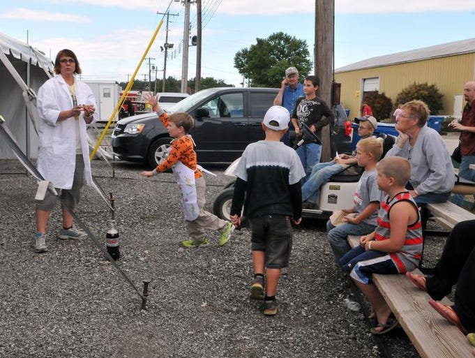 Sandi Brough-Gresh, a Port Clinton native and physics teacher in Michigan, talks to children before making a Mentos bomb during a hands-on science program at the Ottawa County Fair on Wednesday July 16, 2014.