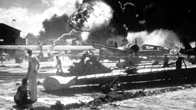 In this Dec. 7, 1941 photo sailors stand among wrecked airplanes at Ford Island Naval Air Station as they watch the explosion of the USS Shaw in the background, during the Japanese surprise attack on Pearl Harbor, Hawaii.