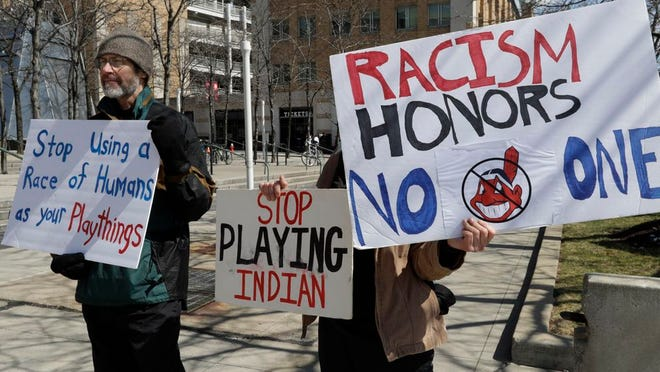 James Watson, left, protests before a baseball game between the Chicago White Sox and the Cleveland Indians, Monday, April 1, 2019, in Cleveland.