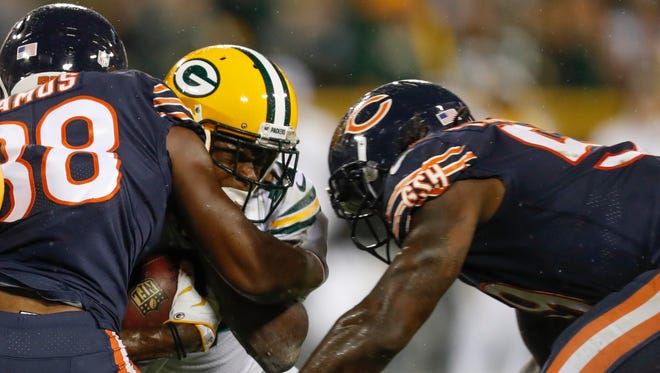 In this Thursday, Sept. 28, 2017, file photo, Green Bay Packers' Davante Adams is hit by Chicago Bears' Adrian Amos and Danny Trevathan during the second half of an NFL football game, in Green Bay, Wis.