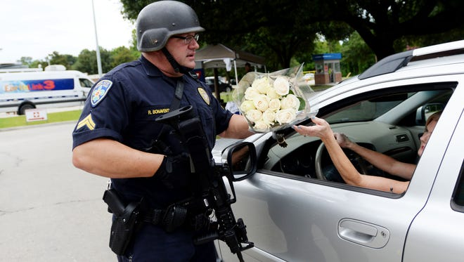Baton Rouge police officer Randy Bonaventure takes a bouquet of flowers at the Our Lady of the Lake Hospital where police officers were brought after the shooting in Baton Rouge.