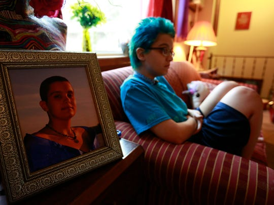 Sam Baum, blurred in background, talks about their gender identity and struggles with suicide in a USA TODAY NETWORK-Wisconsin reporter Liz Welter Monday in Wisconsin Rapids. In the foreground is a photo of Baum taken during a local high school prom. T'xer Zhon Kha/USA TODAY NETWORK-Wisconsin