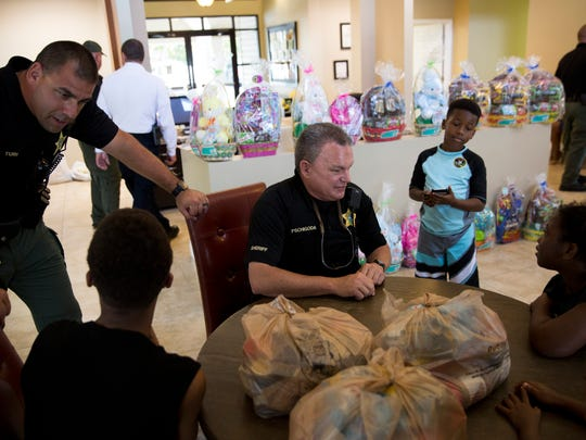 Deputies with the Collier County Sheriff's Office chat with children of the families who lost their homes in the Bear Creek Apartment fire earlier this week at the clubhouse of Bear Creek Apartments Friday, April 14, 2017 in Naples.