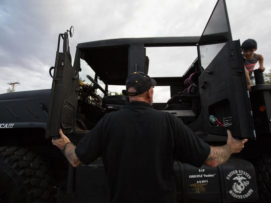 David Mullins, former U.S. Marine, opens the suicide doors on his custom-built truck, named Punisher in honor of Navy SEAL Chris Kyle, while waiting for the start of the 2018 Electric Light Parade at Apodaca Park, Tuesday 3, 2018.