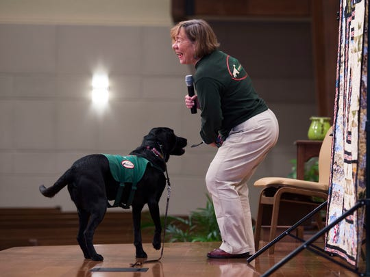"""Laurie Birt works with Smoky Mountain Service Dog Hooligan to demonstrate to attendees his ability to pick up a phone as part of a """"passing of the leash"""" ceremony, which formally gave service dog Vanner to retired Air Force Col. Shawn Pederson at Tellico Village Community Church in Tellico, Thursday, March 1, 2018."""