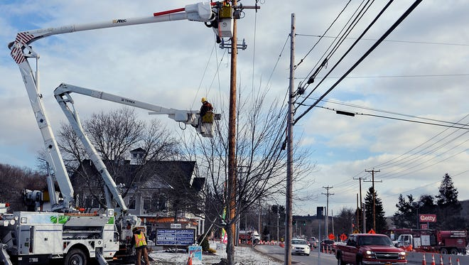 Several crews from Central Hudson Gas & Electric Corporation continue their work on Route 55 in Lagrange, moving power lines from existing poles, right, to new poles, left, that were moved back from the road to make way for three roundabouts in the area. The roundabouts will replace three traffic lights at Arlington High School, Freedom Road and Freedom Business Center. At the top is John Koenig, a Central Hudson working foreman, and below him is Justin Hogarth, a first-class lineman.