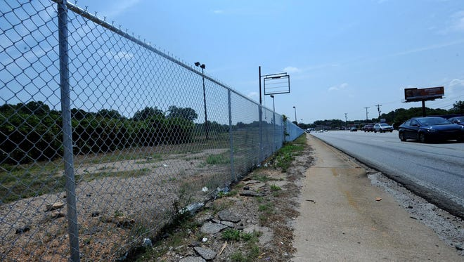 A fence surrounds a piece of property near North Pleasantburg Drive and Furman Hall Road.