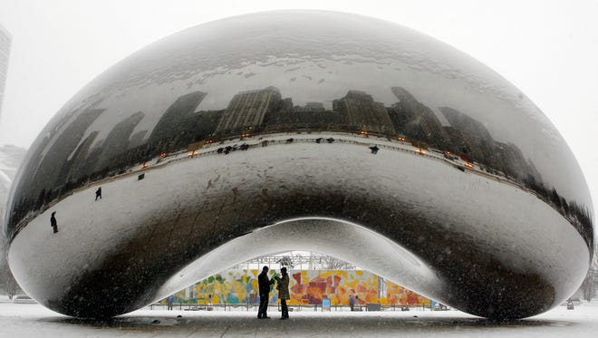 """A couple check out their reflections on the underside of the 110-ton stainless steel Anish Kapoor sculpture – called """"Cloud Gate"""" but better known as """"The Bean"""" – at Millennium Park in Chicago."""