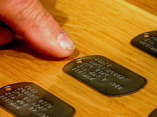 The dog tag representing James Burke, wh was killed in action in Vietnam, is one of 486 dog tags sealed into the bar top at the Fremont VFW Post 2947.