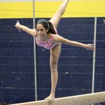 Northville's Disha Satapathy competes on the balance beam at the annual 'Pink Out' meet held at Walled Lake Central.