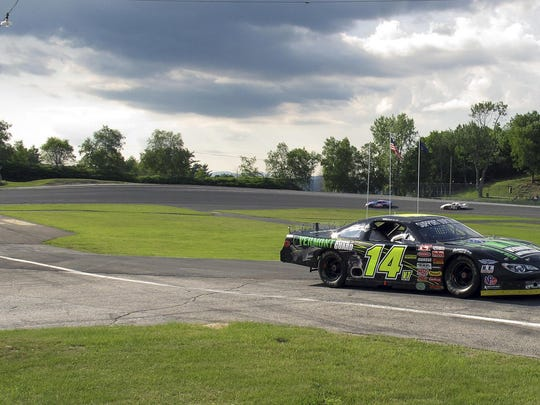 In this July 6 photo, Vermont Gov. Phil Scott drives his No. 14 stock car during a practice run at the Thunder Road in Barre.