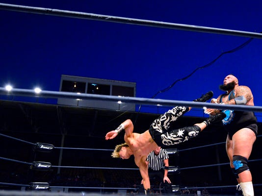 DJ Zema Ion hits Tyrus with a flying kick during Impact Wrestling at the York Fair, Thursday September 17, 2015. John A. Pavoncello - jpavoncello@yorkdispatch.com