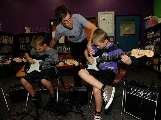 Aaron Gomes talks to Porter Tanner, 10, and Carson Tanner, 8, about playing the electric guitar during the Sound N Vision Summer Youth Music & Art Exploration in 2012 at the Boys and Girls Club in Visalia.
