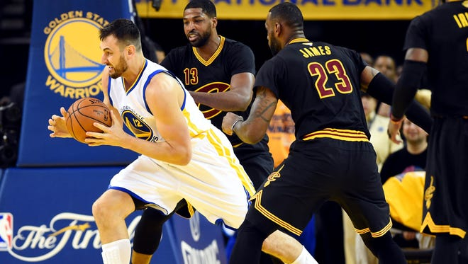 Golden State Warriors center Andrew Bogut (12) handles the ball against Cleveland Cavaliers center Tristan Thompson (13) and forward LeBron James (23) during the first quarter in Game 5 of the NBA Finals at Oracle Arena.