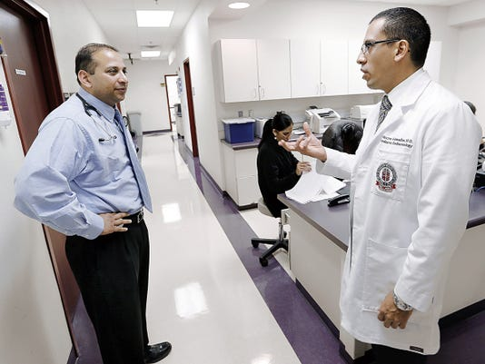 MARK LAMBIE-EL PASO TIMES   Dr. Hector Granados (white jacket) confers with Dr. Chetanbabu Patel at the Children & Adolescent Gender Clinic at the Texas Tech University Health Science Center.
