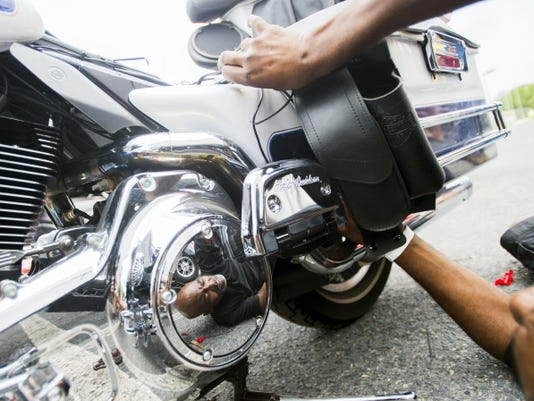 The face of Jamal Pope is reflected in the chrome of a Harley-Davidson motorcycle as he works on installing a ground light kit Friday at Bike Week at the Allstar Events Complex in Gettysburg. Pope runs his own business called Light Me Up Cycles based in Philadelphia and was a vendor at the bike show this week in Gettysburg.