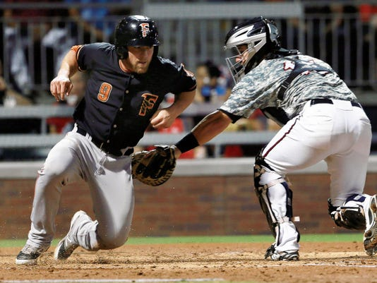 VICTOR CALZADA-EL PASO TIMES Fresno's Nolan Fontana, left, evaded a tag by El Paso catcher Jason Hagerty to score during the second inning Friday.