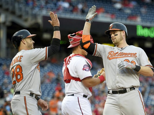 Baltimore's Matt Wieters, right, celebrates his two-run home run with Steve Pearce (28) as Washington Nationals catcher Wilson Ramos, center, looks on during the eighth inning on Thursday in Washington. The Orioles won 5-4.