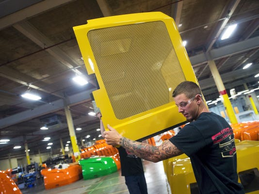 Ben Hughes moves a painted hood to get it ready for shipping at McClarin Plastics.