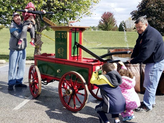 Kids and adults try out a hand-drawn pumper at last year's fire muster. This year's event is Sunday at Cousler Park in Manchester Township.