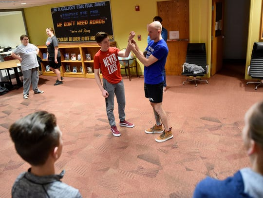 Newark jiu-jitsu instructor Jon Borrows (right) demonstrates how to break a wrist hold with help from Isaac Barsotti, 14, during a self-defense course for teenagers on Monday, March 12 at the Granville Public Library.