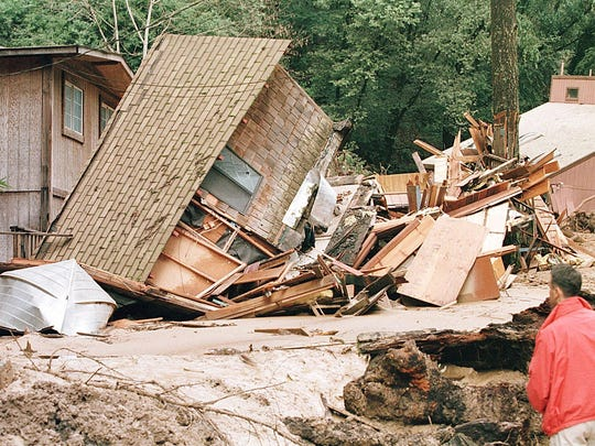 An unidentified man inspects a home that was damaged by a mudslide in Rio Nido, California in 1998. California saw widespread flooding and mudslides that caused more than half a billion dollars in damage.