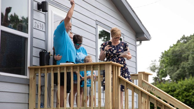 Jeffrey Carpenter holds up the keys to his brand new home with his family during the Topeka Habitat 109th home dedication ceremony Saturday morning.