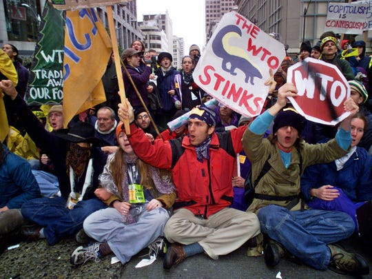 Anti-World Trade Organization protesters chant and wave signs as they sit on the street downtown in Seattle Tuesday. Nov. 30, 1999. Thousands of protesters braved a cold rain to march through Seattle streets Tuesday in an effort to disrupt a meeting of the World Trade Organization, which unions, environmentalists and human rights groups hold responsible for the failings of global capitalism.