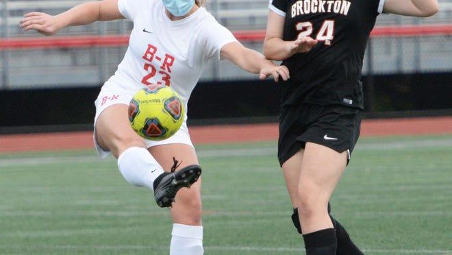 Bridgewater-Raynham's  Isabella Calvani kicks the ball away from Brockton's Emma Demita during their game on Wednesday, Oct. 7, 2020.    Marc Vasconcellos/The Enterprise)