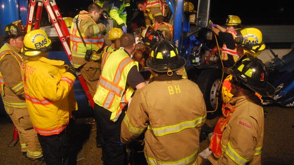 Firefighters and other first responders work at the scene of an accident on I-495 in June of 2013.