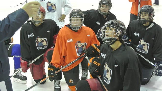 Celeste Brown, orange jersey, listens to her coach during practice with the New York Riveters. Brown is playing with the new National Women's Hockey League.
