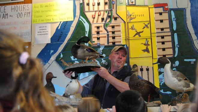 Wildlife biologist Terry McFadden holds up a mallard duck to a group of Algonac kindergarteners early Tuesday afternoon. The class of 22 stopped by the Harsens Island Department of Natural Resources office as part of a field trip with Superintendent John Strycker.