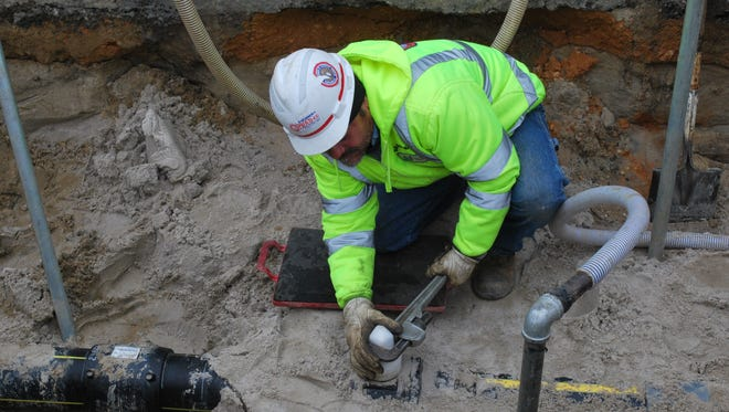 New Jersey Natural Gas said customers will get a bill credit this coming winter. Carlos Rojas, a New Jersey Natural Gas foreman, works on Long Beach Island in this file photo.