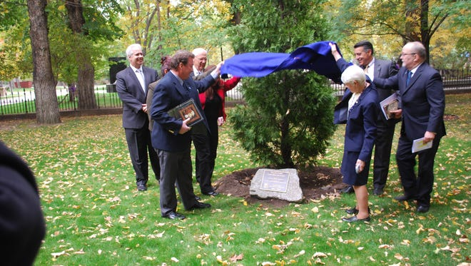 Nevada Gov. Brian Sandoval, second from right, helps members of the Nevada 150 commission unveil a plaque dedicating an incense cedar tree in honor of the state's 150th year. The event culminated the state's celebration of its 150th year of statehood. It turns 151 on Saturday.