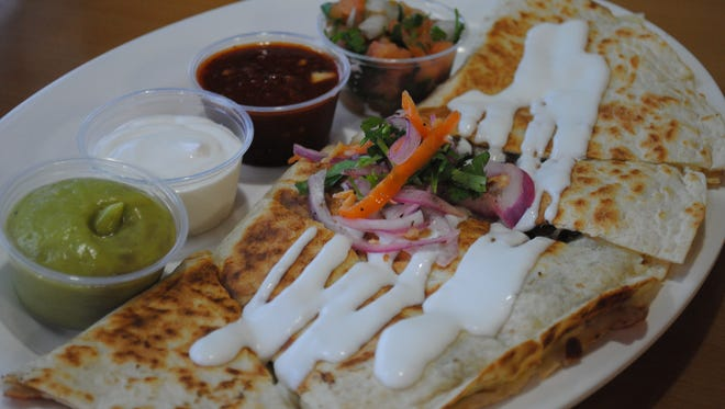 The quesadilla at Tacos SInaloa with meat, cheese, sour cream and an assortment of sauces.