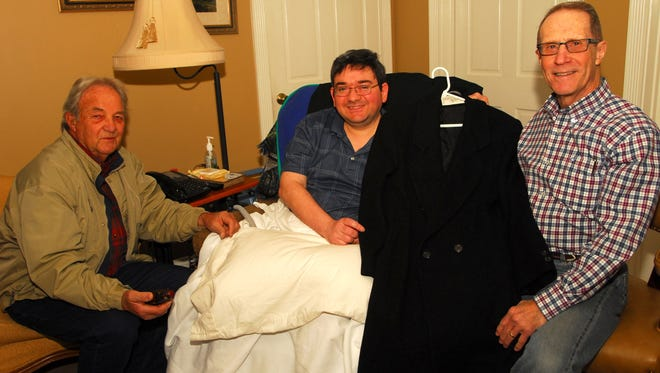 Morgan LeBlanc, Sen. Dudley J. LeBlanc's youngest son, Robert B. Vincent, chairman of the Acadian Museum's exhibition committee Warren Perrin, museum director with one of the senator's coats that will be part of the exhibition going up in the spring.