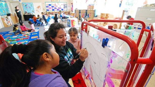 At the Hebbron Family Center in Salinas, assistant Matilde Pe–ña draws a tropical island on which children in the Tiny Tots program will paint.