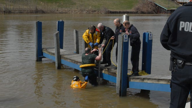 Rescue personnel assist a man from the Black River near the Seventh Street Bridge.