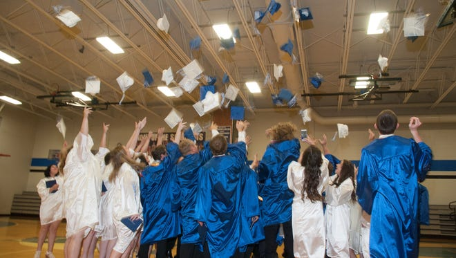 The McConnellsburg High School Class of 2016 celebrate their graduation by throwing their caps into the air.