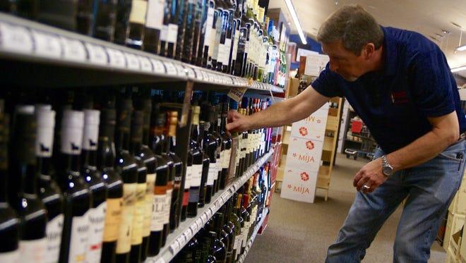 Royce Pharr, an employee at Bluegrass Beverages, arranges wine bottles at the Hendersonville store June 17.