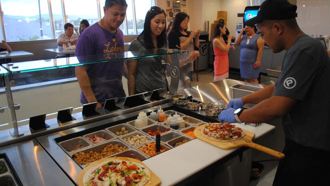 Michael and Aileen Honrado choose their pizza toppings at Pieology in Tamuning on May 19, 2016.